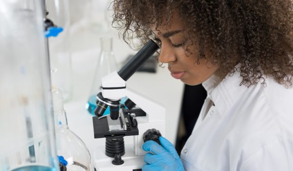 Young Scientist Looking Through Microscope In Laboratory, Mix Race Researcher Doing Research Experiments In Modern Lab